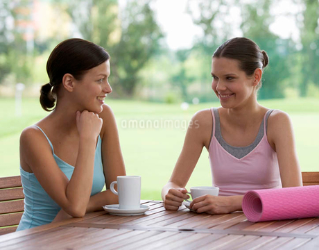 Two young women drinking coffee after a yoga classの写真素材 [FYI02119813]