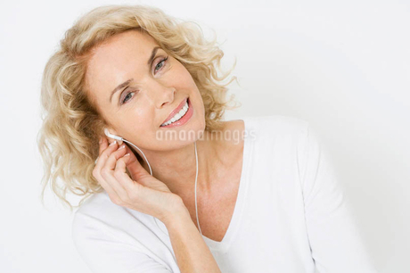 A middle-aged woman listening to mp3 music playerの写真素材 [FYI02119851]