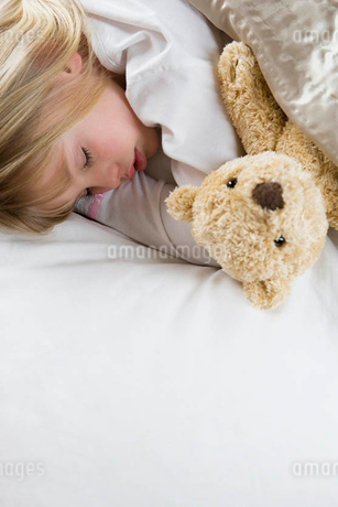 Young girl asleep in her bed with a teddy bearの写真素材 [FYI02119858]