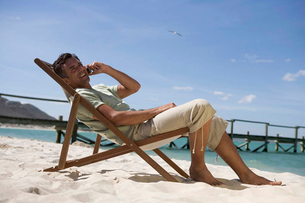 A mature man sitting in a deck chair on a cell phoneの写真素材 [FYI02119862]