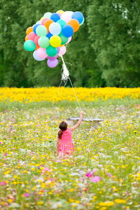 Girl holding bunch of balloons among wildflowers in sunny meadowの写真素材 [FYI02119876]