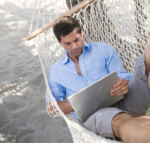 A man using a laptop whilst lying in a hammockの写真素材 [FYI02119888]