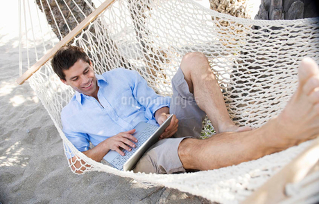 A man using a laptop whilst lying in a hammockの写真素材 [FYI02119891]