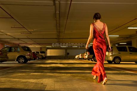 A woman in evening dress walking in a car parkの写真素材 [FYI02119901]