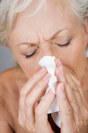 A senior woman blowing her noseの写真素材 [FYI02119913]