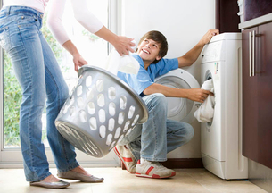 A mother and son loading the washing machineの写真素材 [FYI02119918]