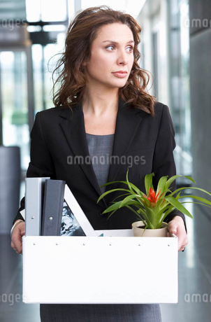 A redundant businesswoman taking her belongings home in a boxの写真素材 [FYI02119935]
