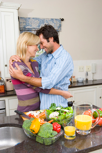 Young couple embracing in kitchen by bowl of salad and jug of juice, side viewの写真素材 [FYI02119936]
