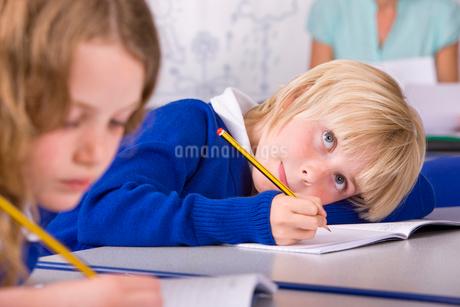 School boy thinking and writing in workbookの写真素材 [FYI02119950]
