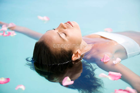 A woman floating in a poolの写真素材 [FYI02119954]