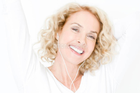 A middle-aged woman listening to mp3 music player, dancingの写真素材 [FYI02119985]