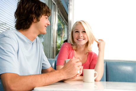 Portrait of a teenage couple flirting in a dinerの写真素材 [FYI02119989]