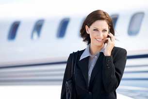 A business woman talking on a mobile phone next to a planeの写真素材 [FYI02119992]