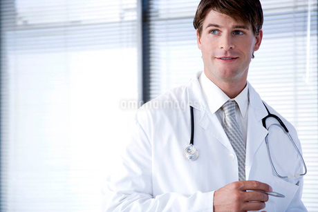 Male doctor in a white coat smilingの写真素材 [FYI02119998]