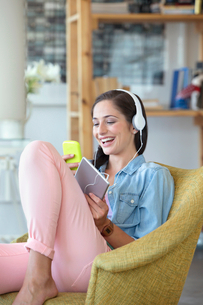 Smiling woman text messaging with cell phone and listening to music on headphones with digital tableの写真素材 [FYI02120051]