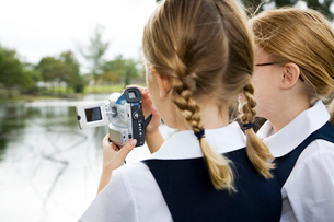 Two schoolgirls using a video cameraの写真素材 [FYI02120061]