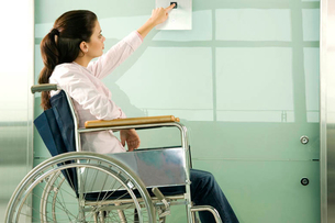 A woman in a wheelchair pressing the button for a liftの写真素材 [FYI02120097]