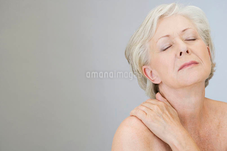 A senior woman with shoulder tension or back acheの写真素材 [FYI02120102]