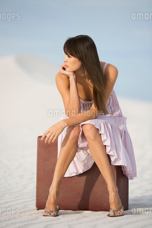 A young woman sitting on a suitcase in the desertの写真素材 [FYI02120123]