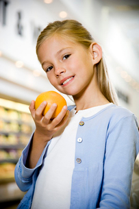 Portrait of a young girl holding a grapefruit in a supermarketの写真素材 [FYI02120127]