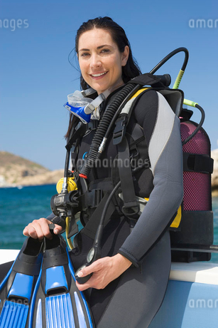 A female scuba diver sitting on a boatの写真素材 [FYI02120138]
