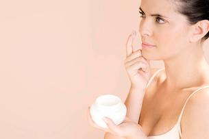 Woman applying moisturising cream to her faceの写真素材 [FYI02120159]