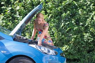 Woman With Broken Down Car Looking Under Bonnetの写真素材 [FYI02120177]