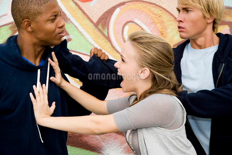 Two men fighting over a girl in front of a graffiti covered wallの写真素材 [FYI02120185]