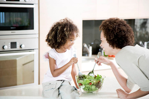 Mother and young daughter preparing healthy salad lunch togetherの写真素材 [FYI02120215]