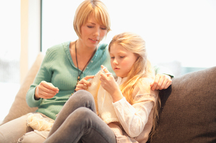 Mother and daughter sitting on sofa knittingの写真素材 [FYI02120236]
