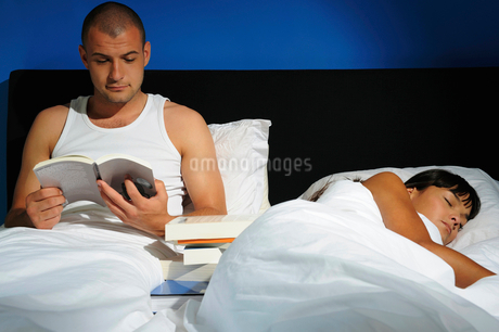 Young man reading while young woman sleeps in bed, studio shotの写真素材 [FYI02120247]