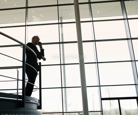 A businessman talking on a mobile phone in a modern office buildingの写真素材 [FYI02120255]