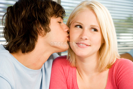 Portrait of a teenage couple with the boy kissing the girlの写真素材 [FYI02120256]