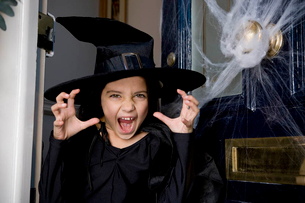 Young  girl at the front door, dressed up as a witch for Halloweenの写真素材 [FYI02120260]