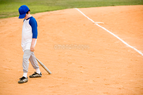 Young boy walking off baseball pitchの写真素材 [FYI02120267]