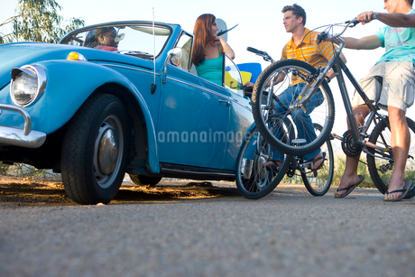 Men on bicycles in conversation with women in car, low angle viewの写真素材 [FYI02120286]