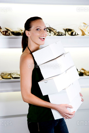 Sales assistant in a shoe shop carrying a stack of boxesの写真素材 [FYI02120290]