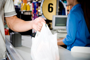 Close up of customer and supermarket checkout assistantの写真素材 [FYI02120294]