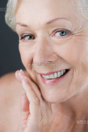 A senior woman touching her cheek, smilingの写真素材 [FYI02120309]