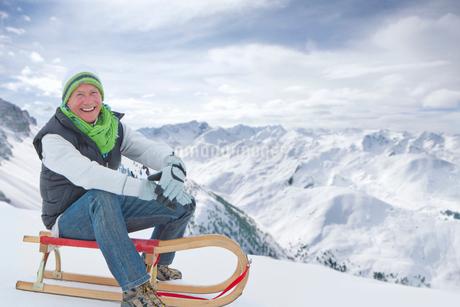 Portrait of smiling senior man sitting on sled on snowy mountainの写真素材 [FYI02120326]
