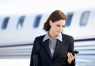 A business woman talking on a mobile phone next to a planeの写真素材 [FYI02120353]