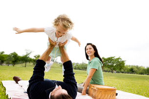 Father lifting up daughter on picnic rugの写真素材 [FYI02120354]