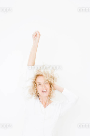 A middle-aged woman listening to mp3 music player, dancingの写真素材 [FYI02120386]