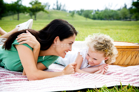 mother and daughter lying on picnic rugの写真素材 [FYI02120403]