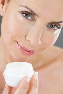 A middle-aged woman holding a pot of moisturising creamの写真素材 [FYI02120435]