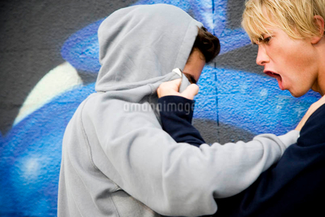 Two men fighting in front of a graffiti covered wallの写真素材 [FYI02120444]