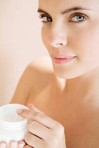 Woman holding a pot of moisturising creamの写真素材 [FYI02120450]