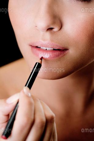 Woman using a lip pencilの写真素材 [FYI02120467]