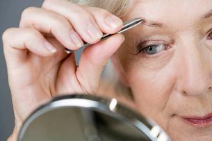 A senior woman plucking her eyebrows with tweezersの写真素材 [FYI02120477]
