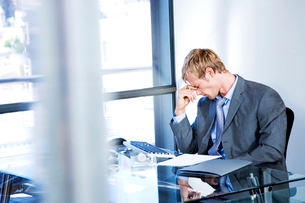 Businessman looking stressed in a modern officeの写真素材 [FYI02120485]
